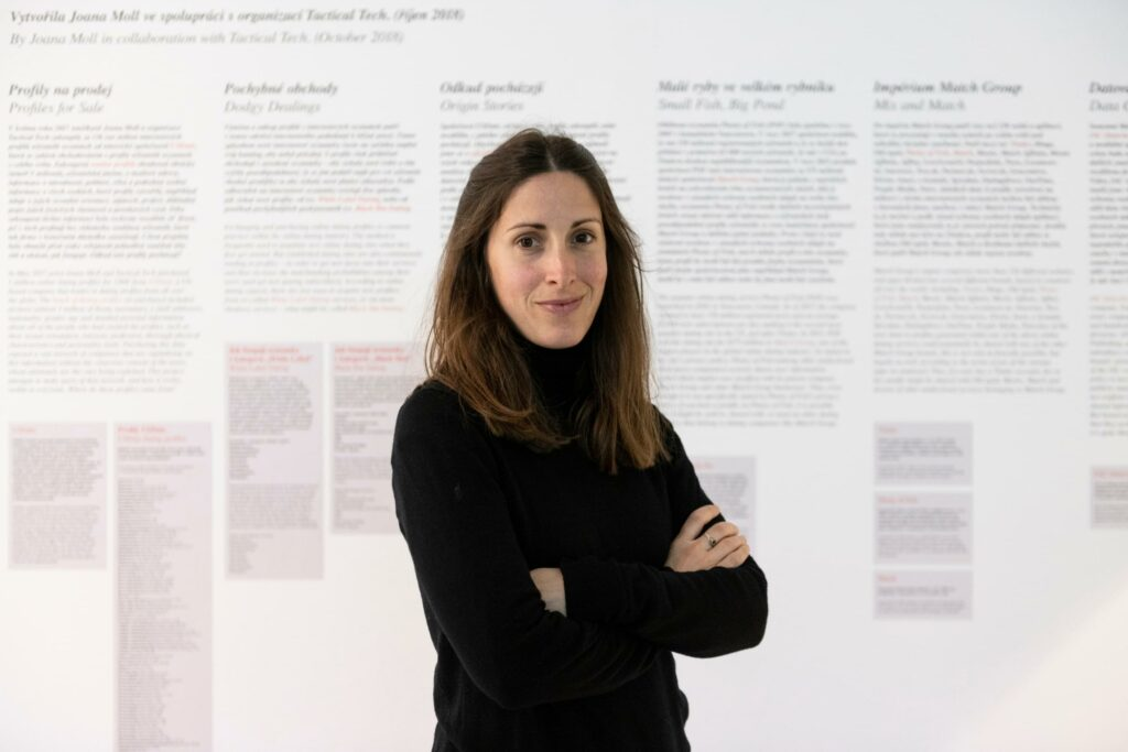 A portrait photo of artist and researcher Joana Moll standing in front of her work