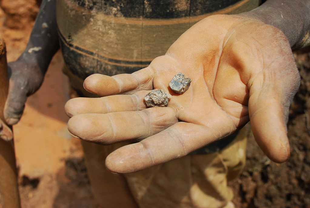 A miner holds up cassiterite, an ore used to smelt tin
